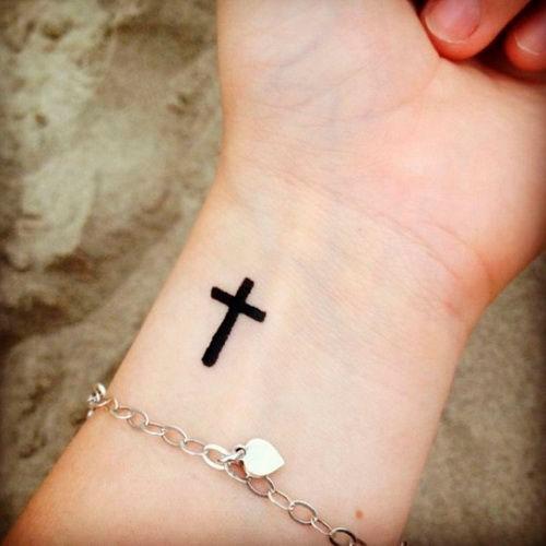 Tatuagem de cruz delicada no antebraço